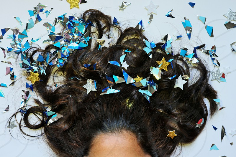 glitter on woman's hair woman laying down top view glitter spread on hair shiny brown and black hair forehead starts gold silver blue glitter photo