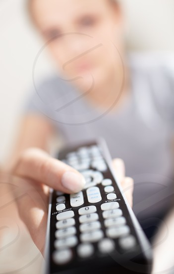 Young woman with remote watching TV. Shallow dof close-up focused on remote control. photo