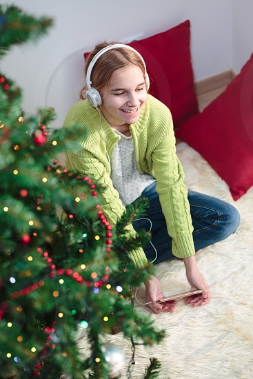 Young girl listening to Christmas carols through her headphones photo
