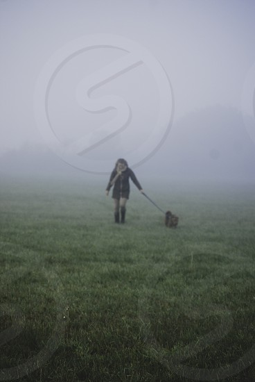 Woman walking her dog in the countryside on a misty Autumn morning. photo
