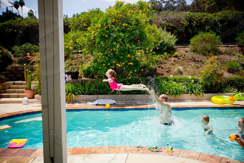 girl jumping on swimming pool beside man photo