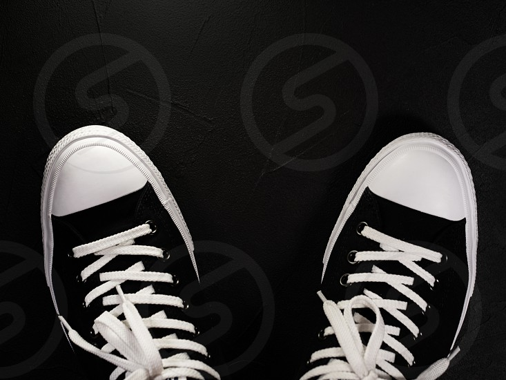 Black sneakers with white shoelaces. Classic vintage trendy shoes on black monocrome background. Copy space. photo