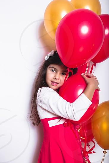 Baby Girl Holding Balloons celebrating her Birthday photo