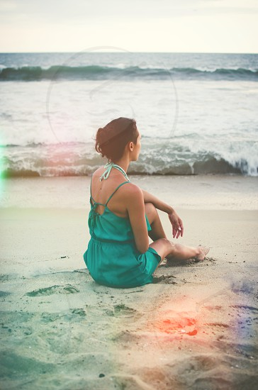 Woman sitting in the sand on a beach with waves in the background. Sunflare effect. photo