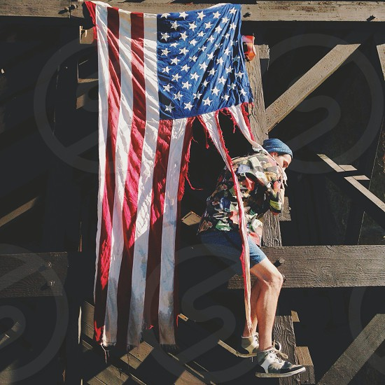 person climbing on wall by torn american flag photo