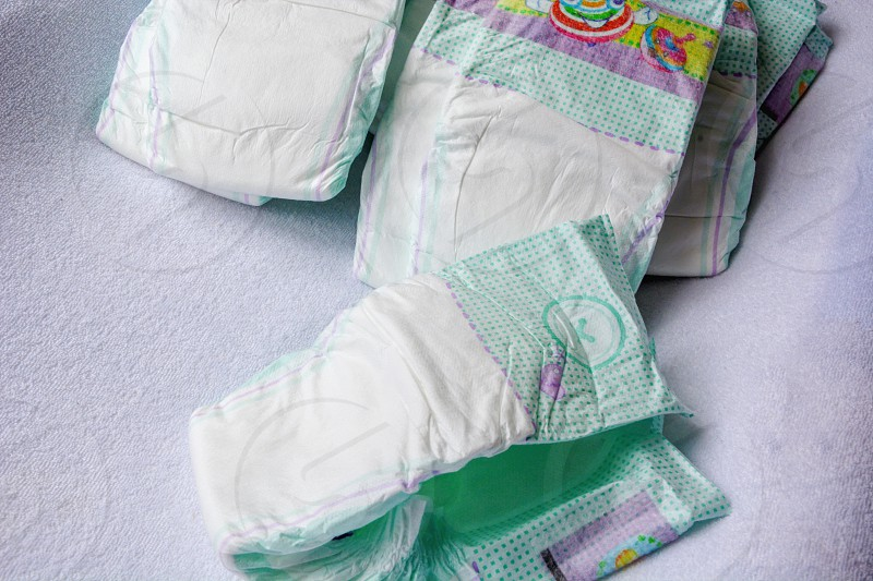 Group of disposable diapers arranged over a white changing table. Hygiene and health care for baby photo