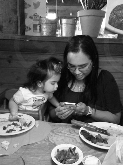 woman and toddler on phone in restaurant photo
