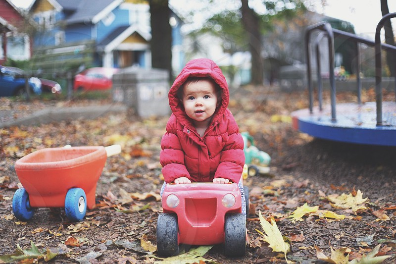 Baby playing on the playground on a rainy Fall day.  photo