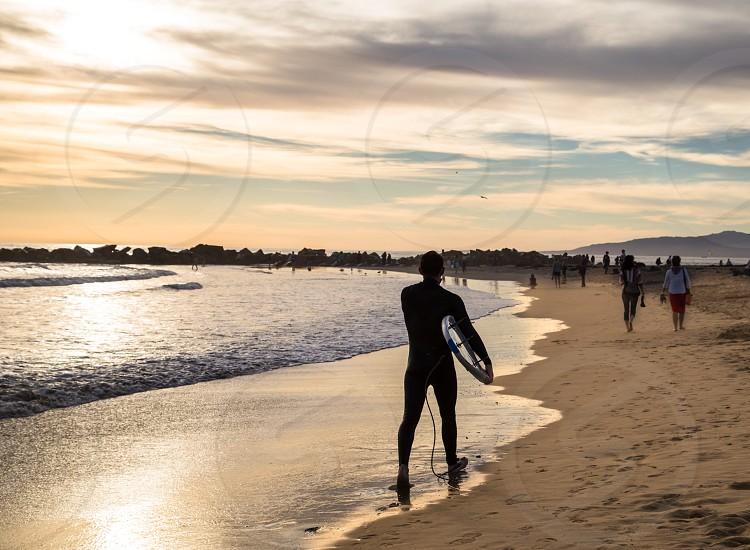 Surfer walking down ocean sunset beach photo