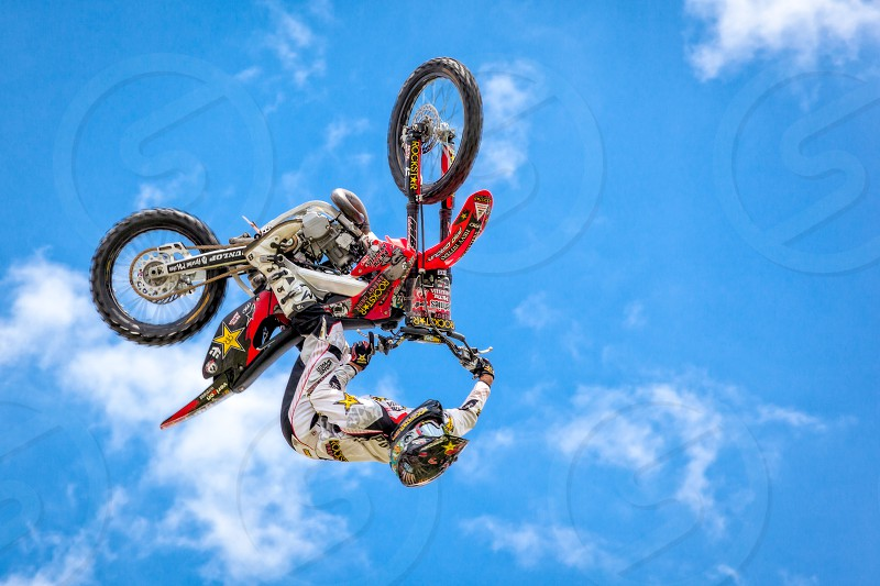 man on red motorcycle doing back flip with motorcycle during daytime photo