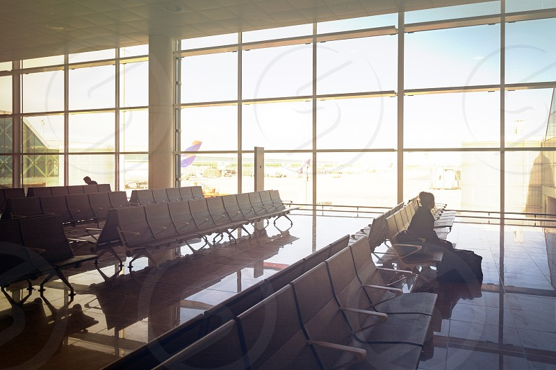 stained glass window of the departure hall inside an airport with a girl sitting on chairs waiting for her flight photo