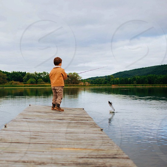 boy in orange jacket fishing photo