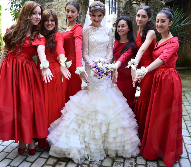 woman in white floral laced scoop neck long sleeve ruffled mermaid dress surrounded by women wearing red dresses photo