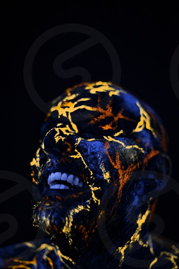 Conceptual Portrait of a man painted in fluorescent UV colors and looks like Neon lava photo