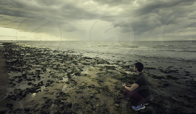Young man with casual clothes squatting on the shores of the Mediterranean Sea among algae on the beach of Sanlucar de Barrameda photo