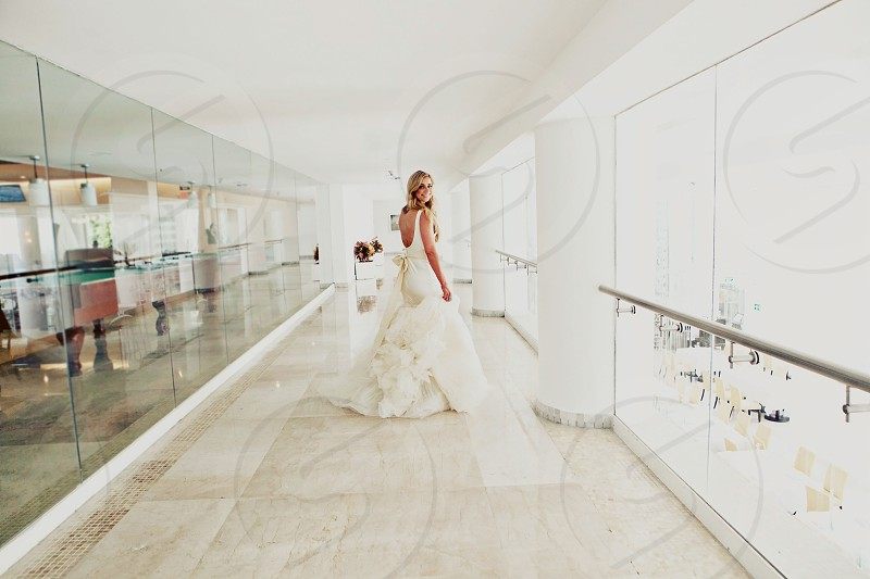 woman in white wedding gown walking in the lobby  photo