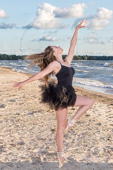woman in black dress posing on beach photo