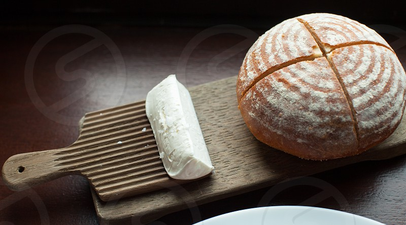 brown round bread at top of brown board beside white rectangular dough photo