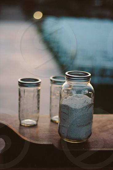 ball mason jar filled with white sand near clear glass mason photo