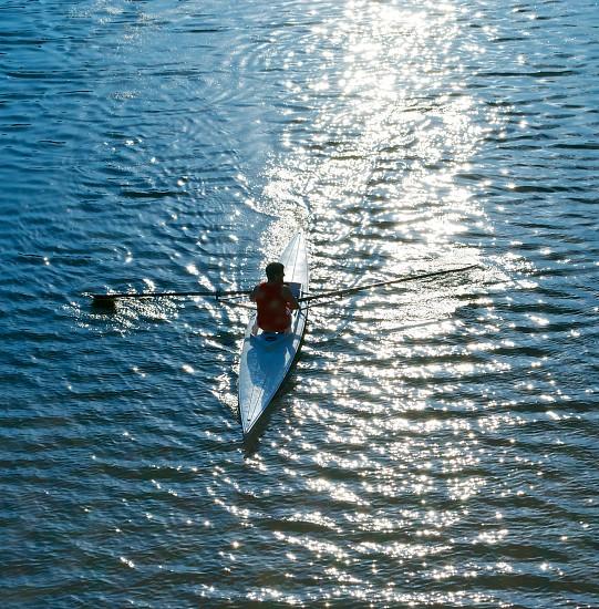 man rowing in blue kayak photo
