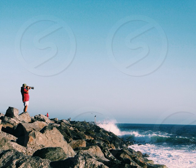 man taking photos of ocean waves crushing on rock formations photo