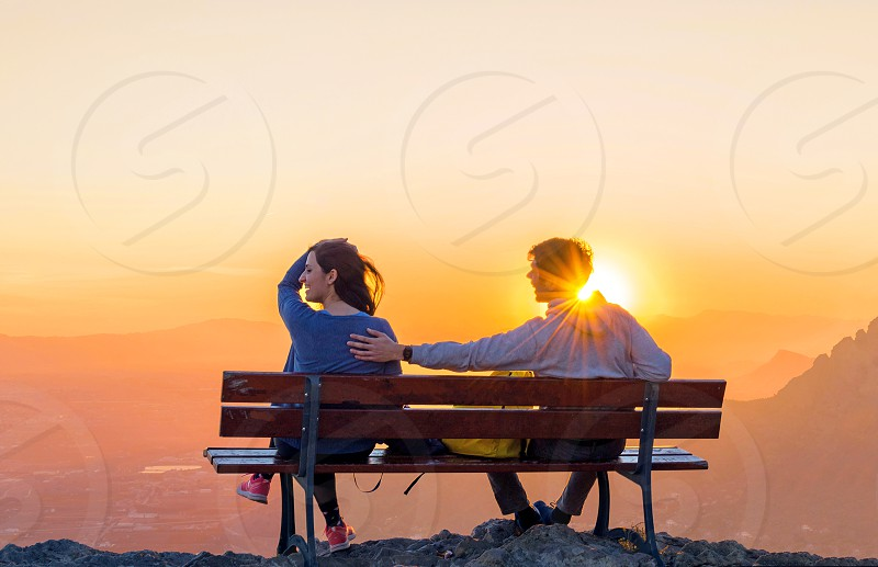Couple sitting together watching the sunset at the top of a mountain photo