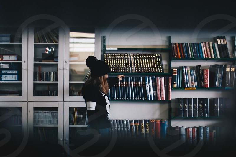 Woman searching for a book in the library. photo