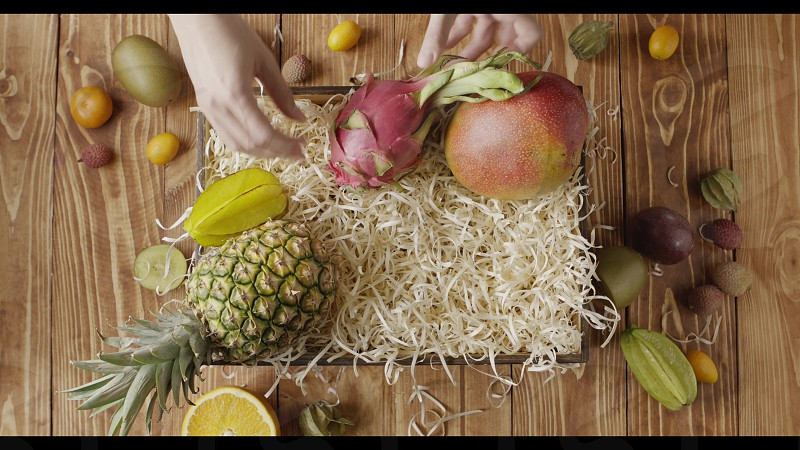 Wooden box for fresh natural organic ripe exotic fruits on a wooden background. Top view girl's hands make composition from tropical fruits. Fast motion 4K UHD video 3840 2160p. photo