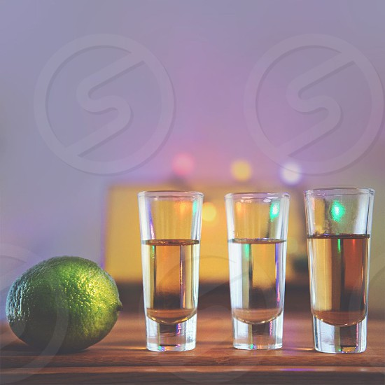 clear liquid in clear shot glasses on table by green citrus photo