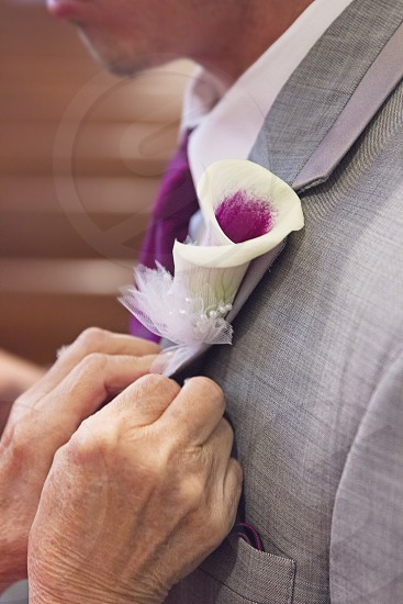 man wearing white and purple flower brooch photo