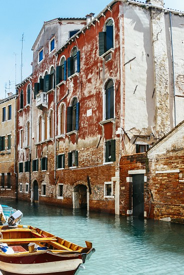 venice building facade door window decaying aged red canal boat patina deteriorating italy house wall photo