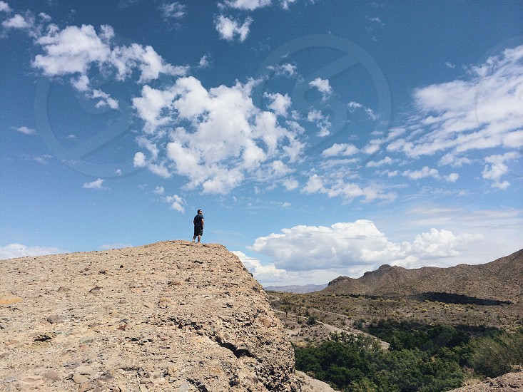 brunet man wearing black standing on gray cliff facing cloudy blue sky photo