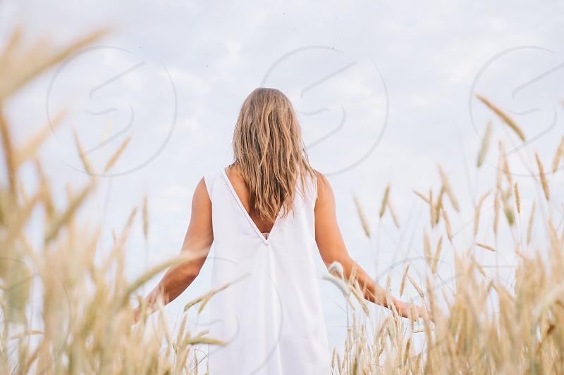 woman wearing white sleeveless dress beside brown grains under white sky during daytime photo