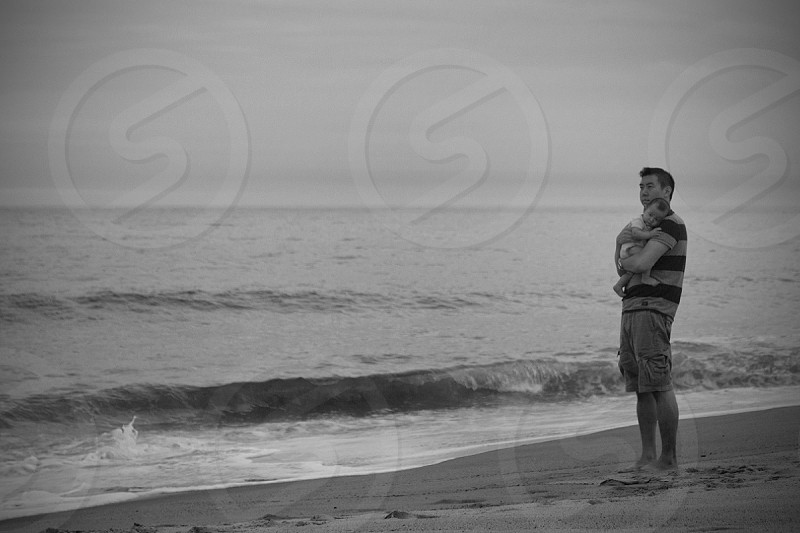 man carrying child on seashore in grayscale photography photo