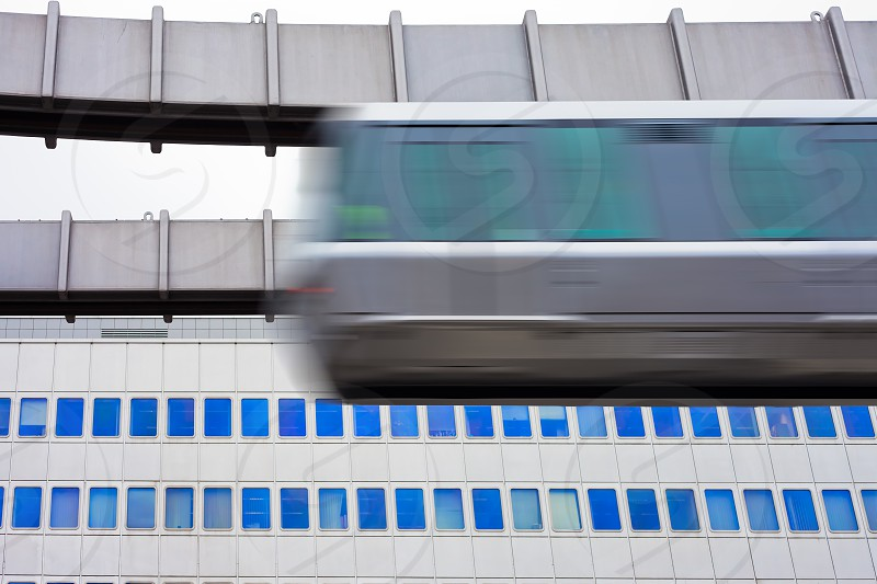 Modern public transportation system skytrain hanging from elevated guideway  passes by in front of tall office building facade (with motion blur) photo