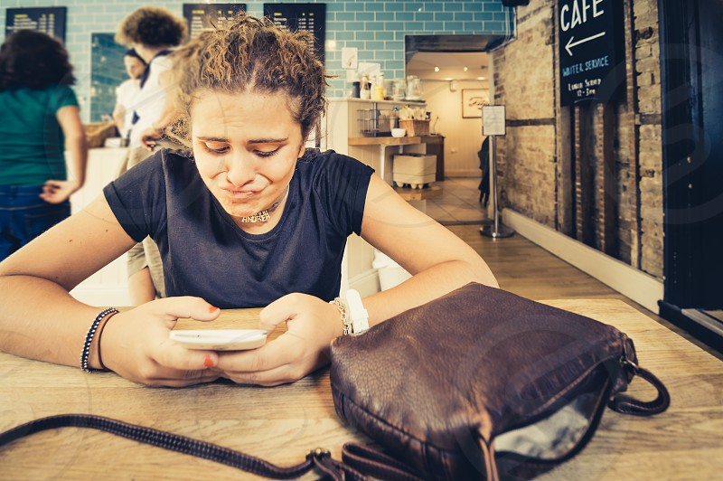 Young watching her smartphone (mobile phone) in a cafe with a weird face. photo