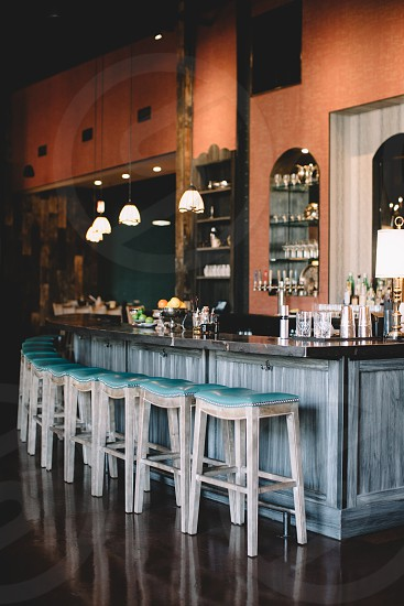 clear brown painted wall bar with gray and black bar counter and white and teal padded stool photo