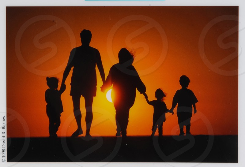 A young family walking on the beach holding hands at sunset. photo