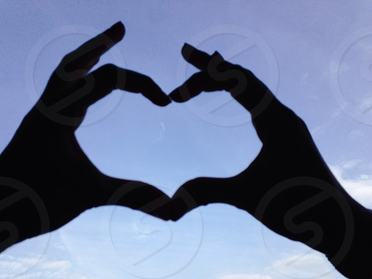 2 people doing heart sign under blue and white sunny cloudy sky photo