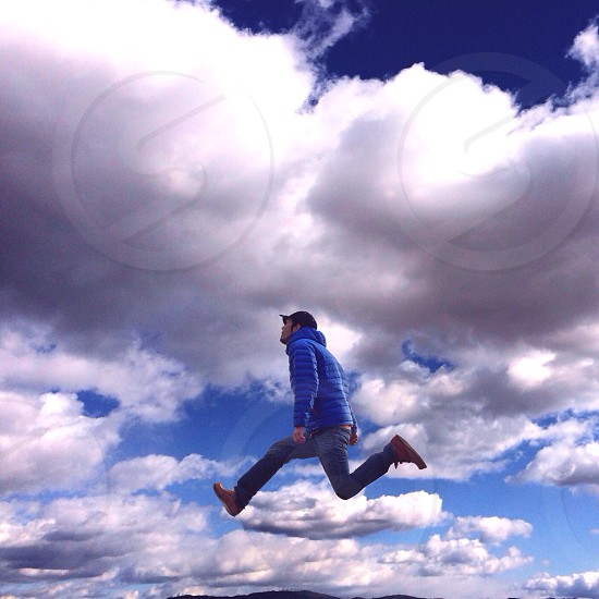 man jumping under cumulus clouds view photo