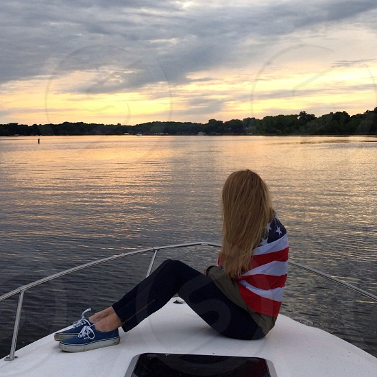 woman wearing blue pants and blue sneakers sitting on yacht photo