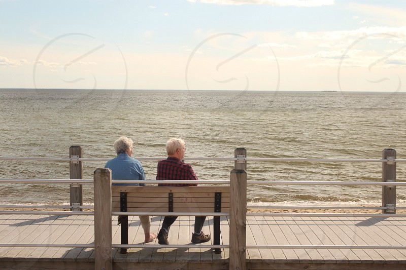 man and woman sitting on beige wooden bench photo