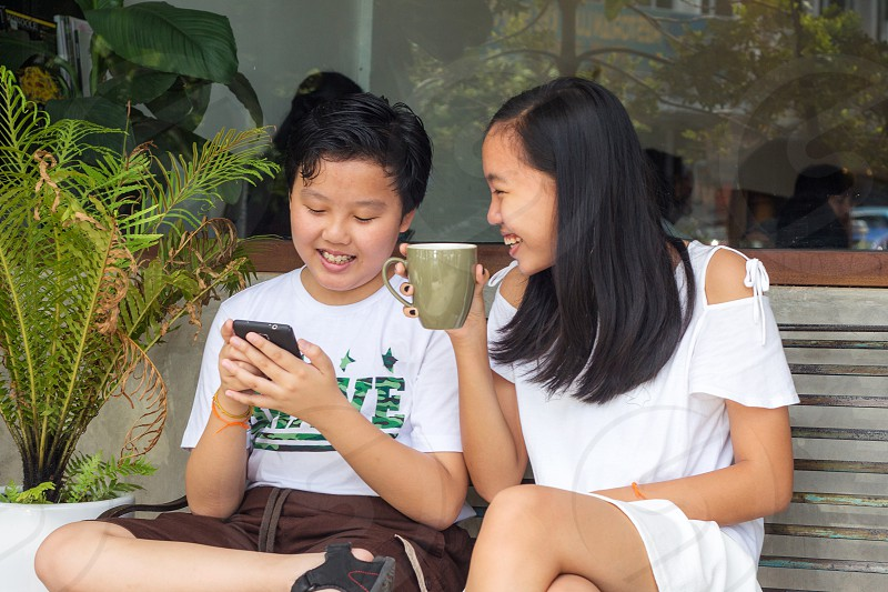 young asian sibling talking to each other in front of a cafe with the brother holding a smart phone on hand photo