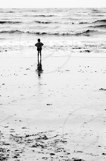 Lone boy  standing on water edge of remote beach photo