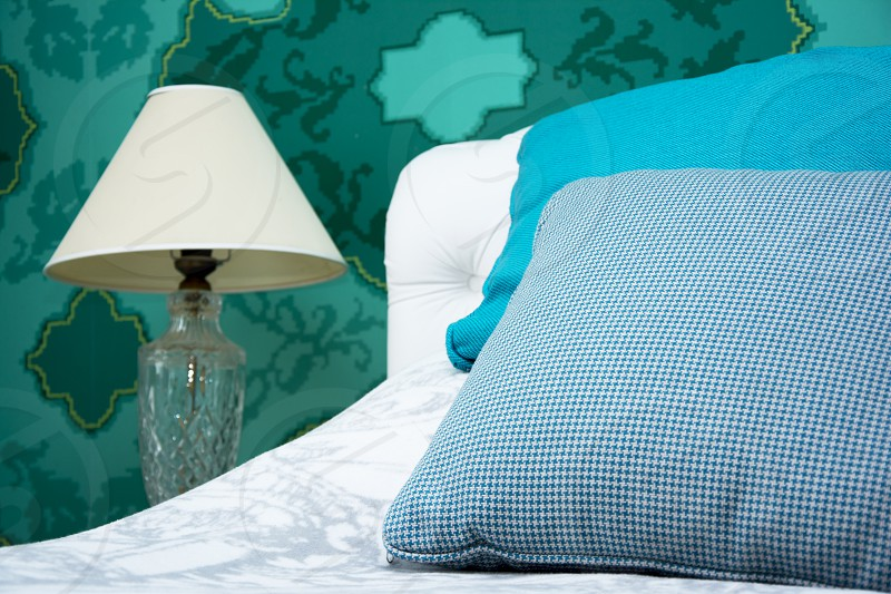 Bedroom with white bedding and turquoise pillows and wallpapers and cute white lamp photo