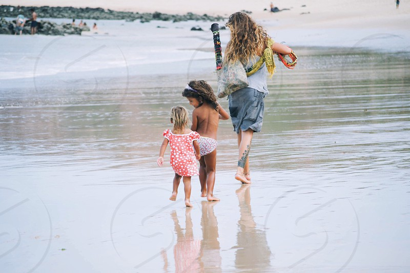 woman and two kids on the beach photo