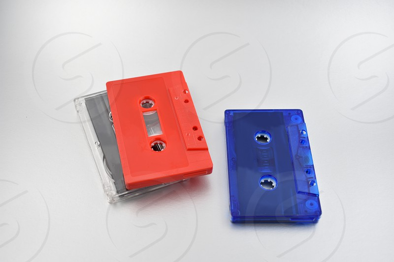 Compact cassettes. Red and blue cassette tape. Compact Audio Cassette on a silver background photo