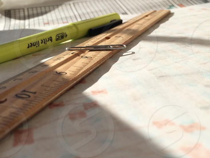 paper clip on brown ruler beside yellow ballpen photo