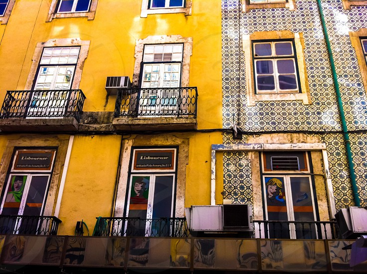 yellow apartment building with balconies during daytime photo