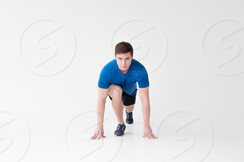 Running man on low start. Stands in rack ready to achieve goals and wins. Young sexy Muscular male athlete wearing sporty blue t-shirt and shorts studio portrait white background.Motivation concept photo